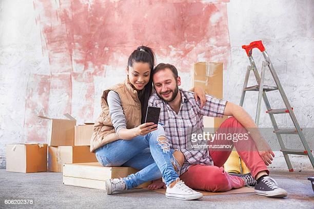 Couple sitting on ground and making selfie at new home
