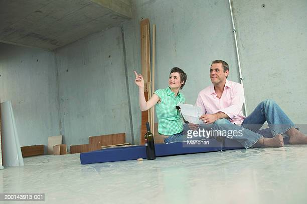 Couple sitting on mattress, with wine, woman pointing