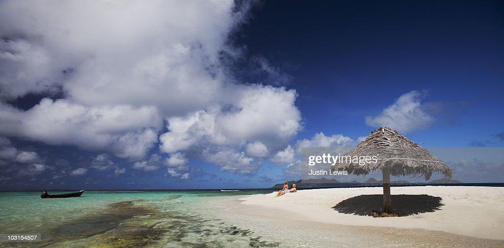 Couple sitting on Mopion Island. : Stock Photo