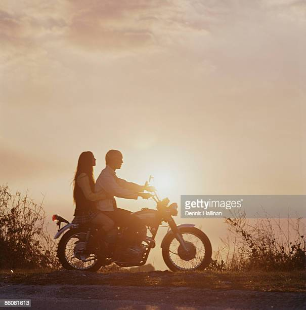 Couple sitting on motorcycle contemplating sunset