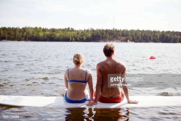 Couple sitting on paddleboard