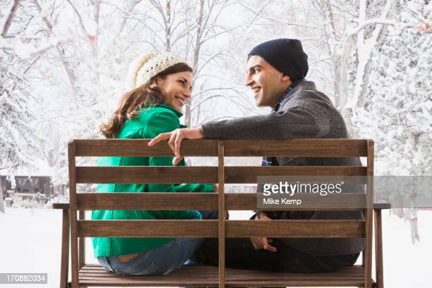 Couple sitting on park bench in snow