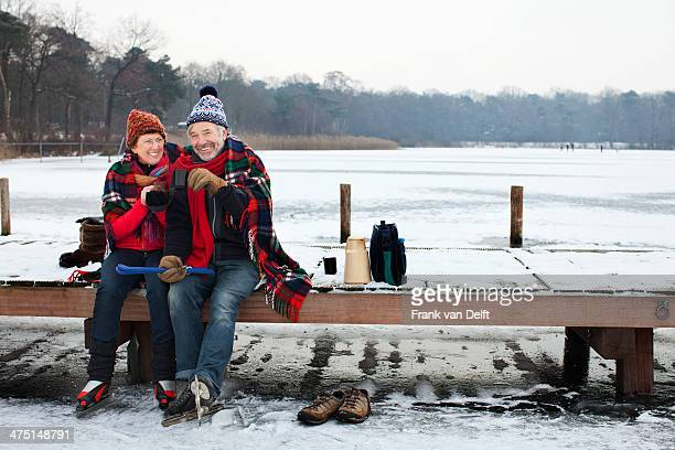 Couple sitting on pier having hot drink