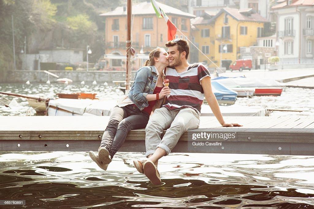 Couple sitting on pier whispering and eating ice cream cone at lake Mergozzo, Verbania, Piemonte, Italy