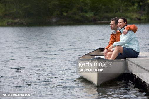 Couple sitting on pier with legs in canoe, looking at view : Stock Photo