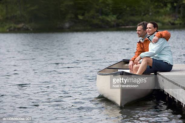 Couple sitting on pier with legs in canoe, looking at view