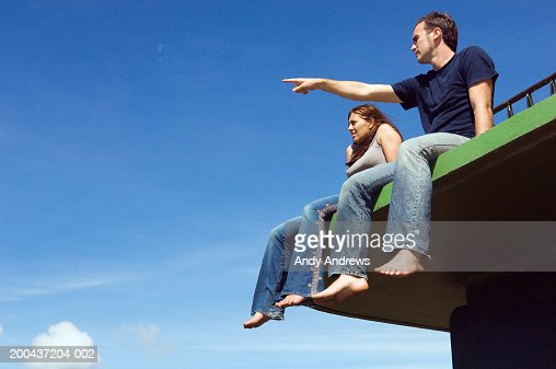 Couple sitting on platform outdoors, man pointing, low angle view : Stock Photo
