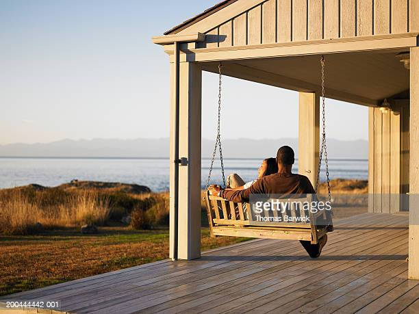 Couple sitting on porch swing overlooking water, dusk, rear view