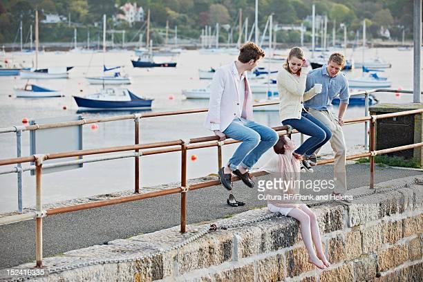 Couple sitting on railing of harbor