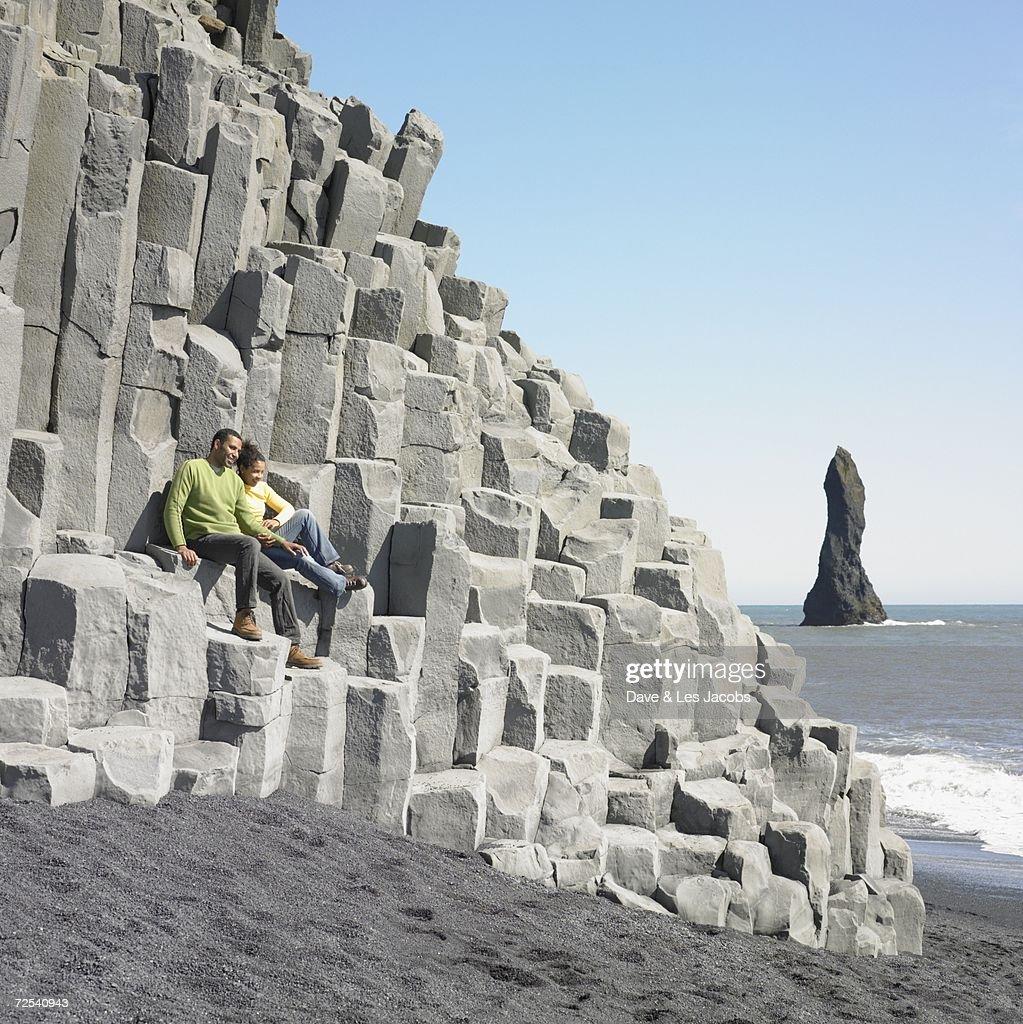 Couple sitting on rock ledge at beach : Stock Photo
