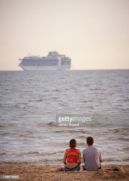 Couple sitting on sand of Port Melbourne beach watching departing cruise ship on Port Philip Bay.