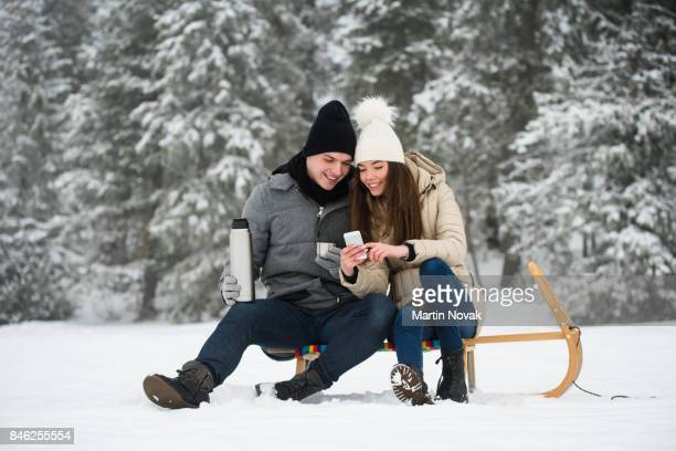Couple sitting on sleigh, enjoying winter holidays