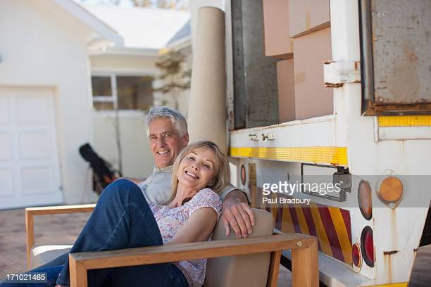 Couple sitting on sofa beside moving van