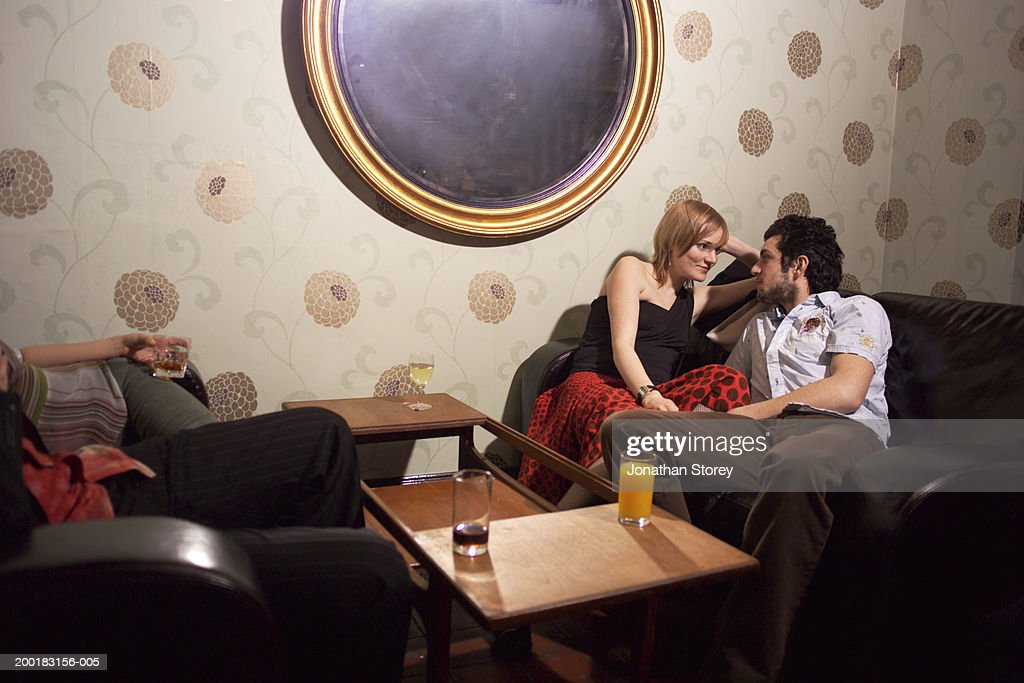 Couple sitting on sofa by drinks, looking at each other