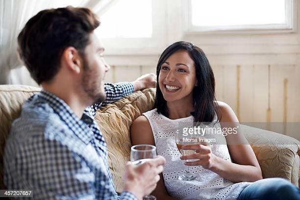 Couple sitting on sofa drinking wine