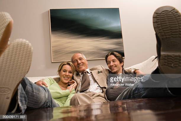 Couple sitting on sofa either side of mature man, feet on coffee table