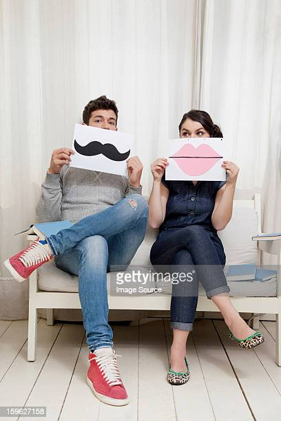 Couple sitting on sofa holding lips and moustache