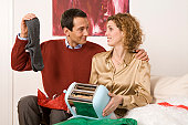 'Couple sitting on sofa, holding toaster and socks'