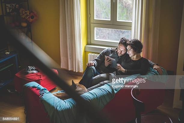 Couple sitting on sofa, looking at digital tablet