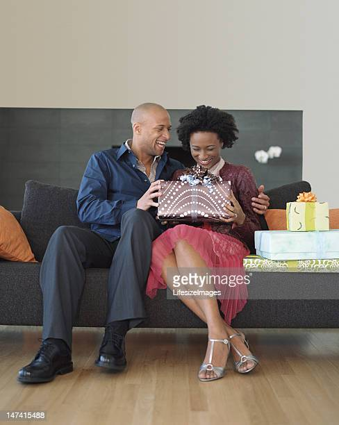 Couple sitting on sofa, man giving woman gifts