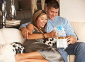 Couple sitting on sofa opening gift box