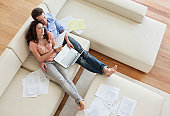 Couple sitting on sofa paying bills together