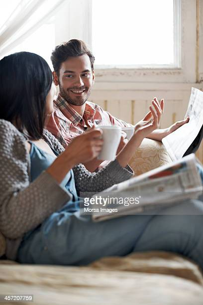 Couple sitting on sofa reading and talking