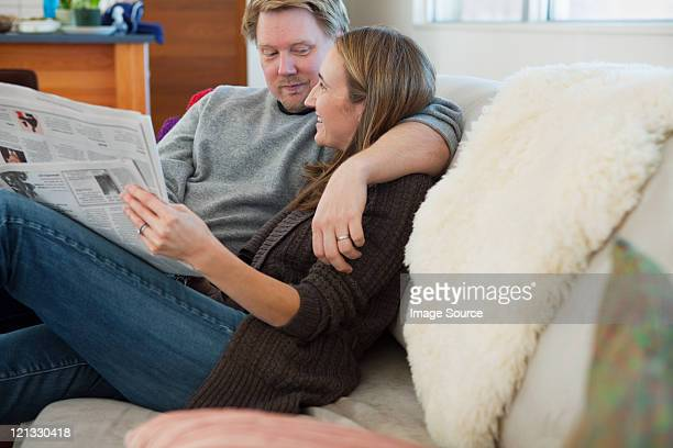 Couple sitting on sofa reading newspaper