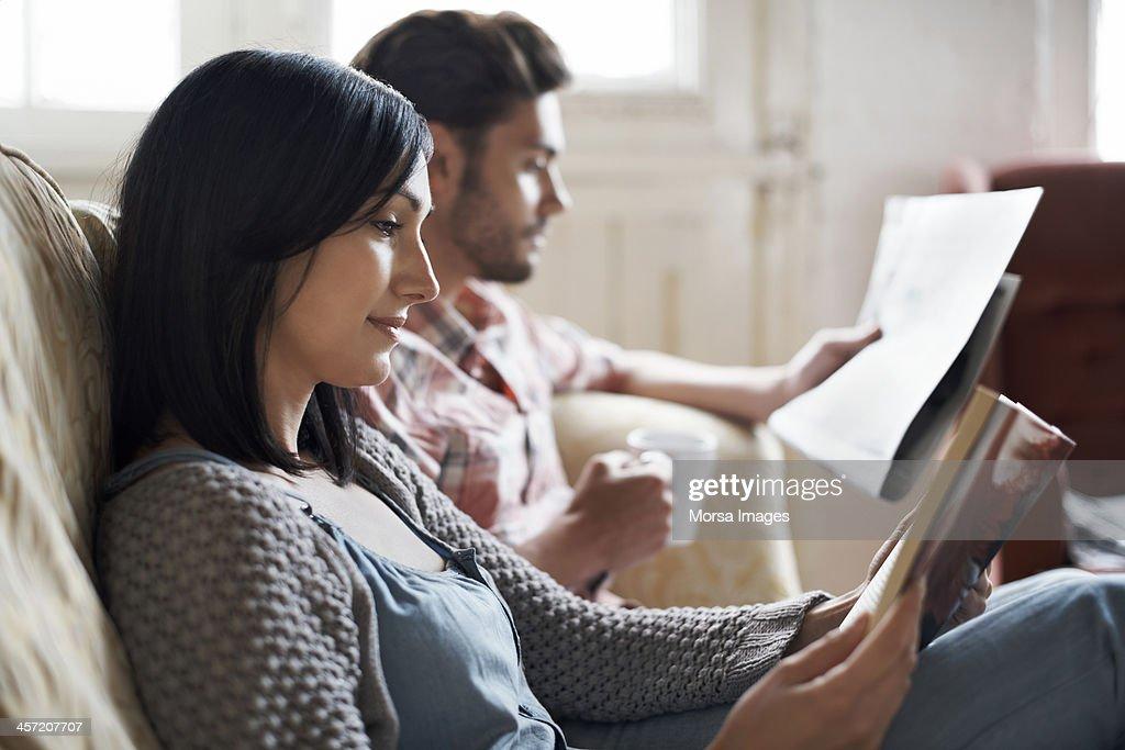 Couple sitting on sofa reading : Stock Photo