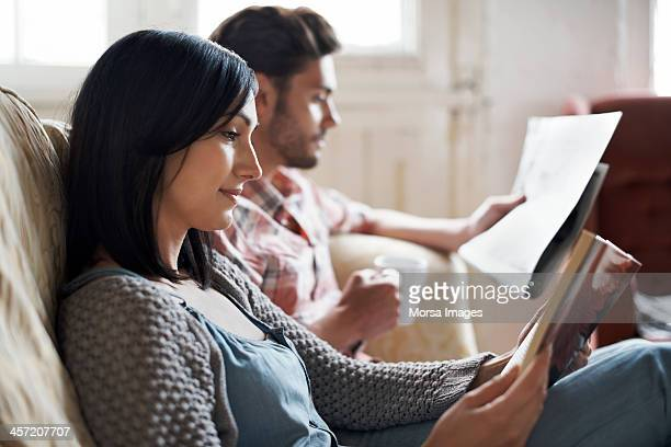 Couple sitting on sofa reading
