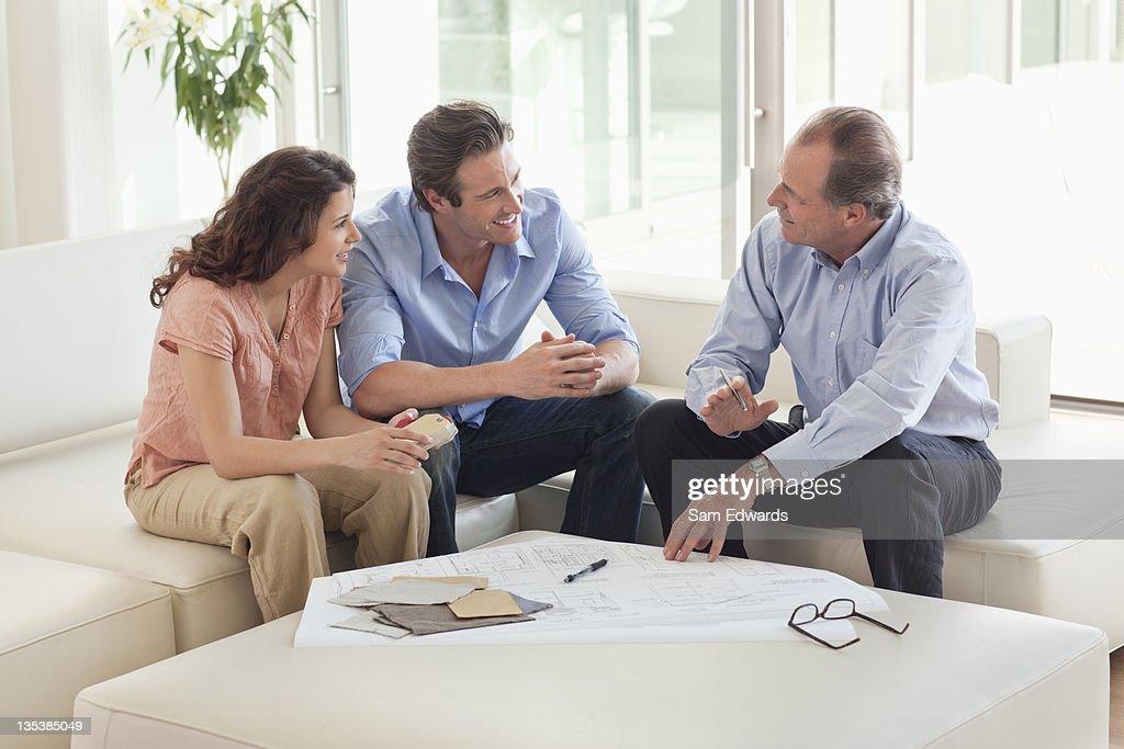 Couple sitting on sofa talking to financial advisor : Stock Photo