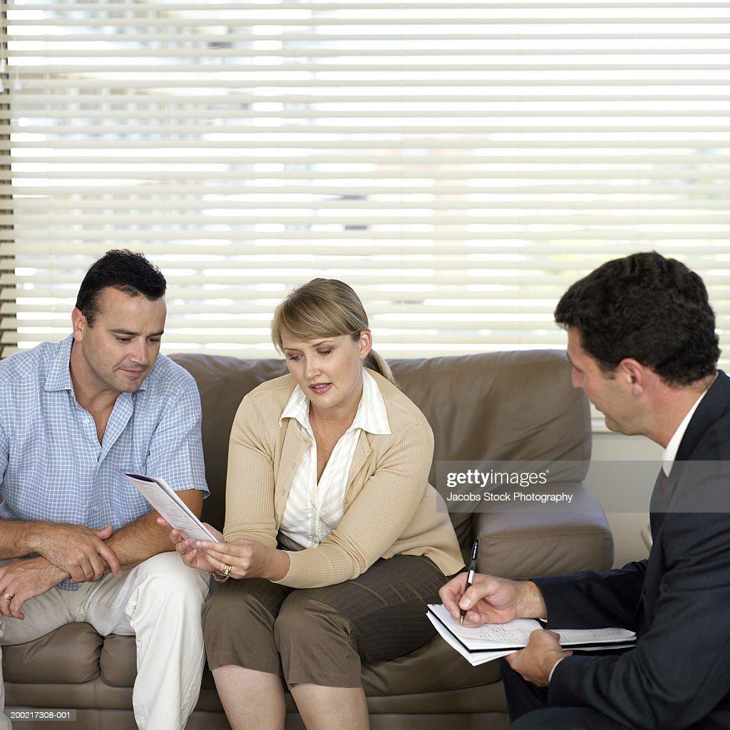 Couple Sitting On Sofa Talking To Male Advisor Stock Photo