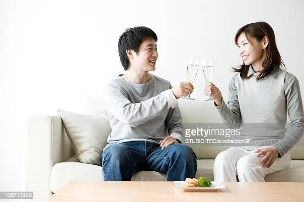 Couple sitting on sofa toasting