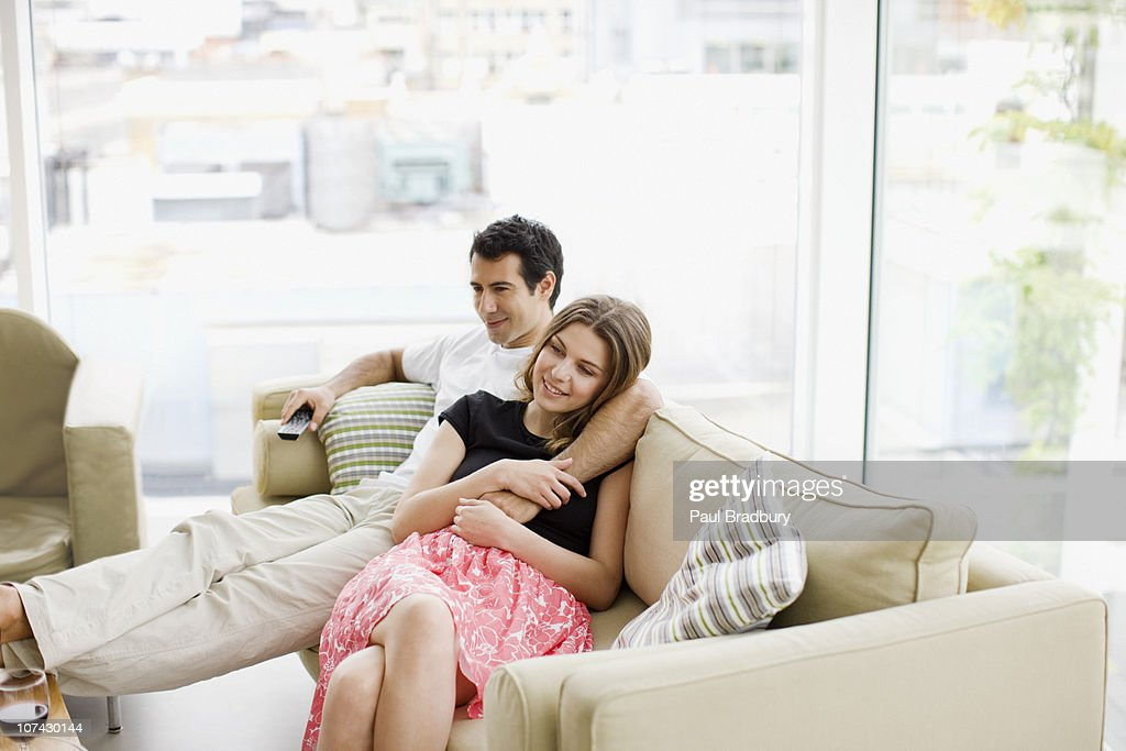 Couple sitting on sofa watching television : Stock Photo