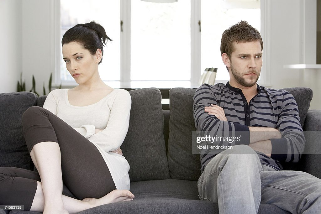 Couple sitting on sofa with arms folded, looking angry : Stock Photo