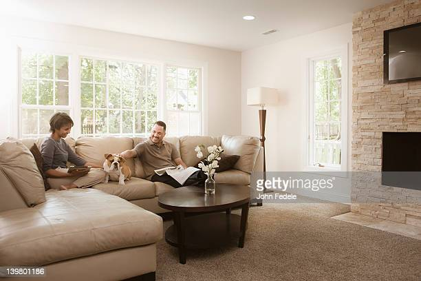 Couple sitting on sofa with English bulldog