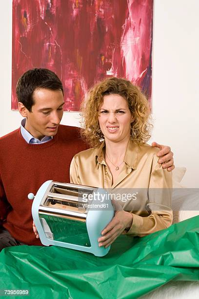 Couple sitting on sofa, woman holding toaster