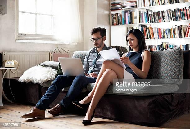 Couple sitting on sofa working