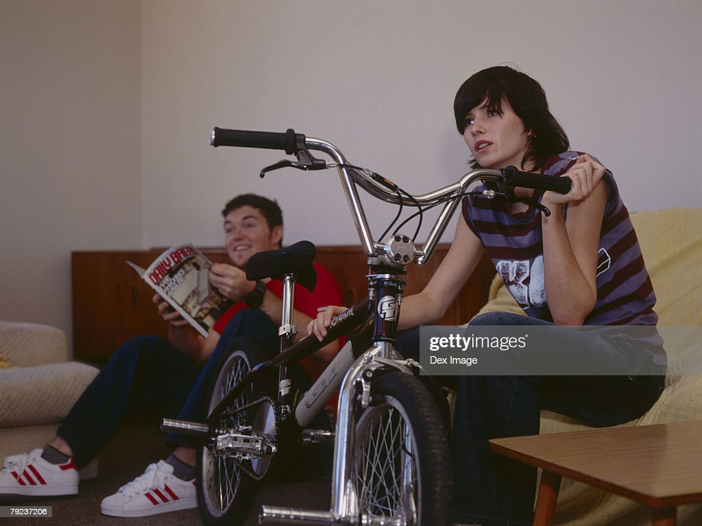 Couple sitting on sofa, young woman supporting bike : Stock Photo