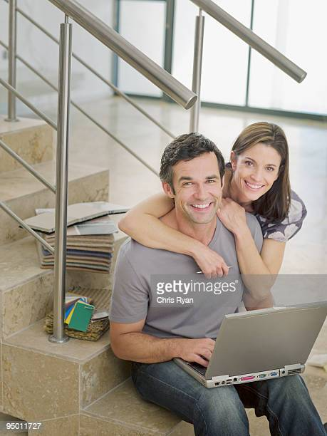 Couple sitting on stair with laptop and paint samples