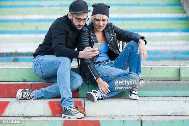 Couple sitting on stairs and using smart phone