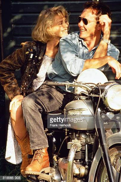 Couple sitting on stationary motorbike