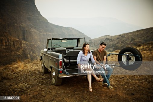 Couple sitting on tailgate of convertible : Stock Photo