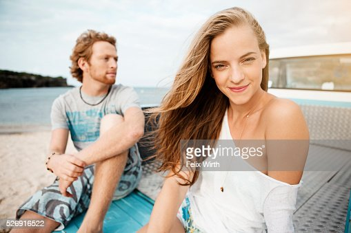 Couple sitting on tailgate of truck on beach : Stockfoto
