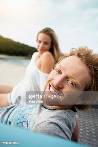Couple sitting on tailgate of truck on beach : Bildbanksbilder