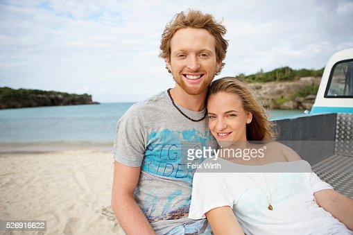 Couple sitting on tailgate of truck on beach : Foto de stock