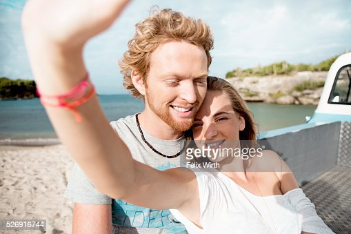 Couple sitting on tailgate of truck on beach : Stock-Foto