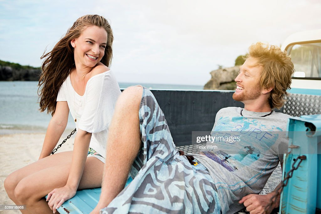 Couple sitting on tailgate of truck on beach : ストックフォト