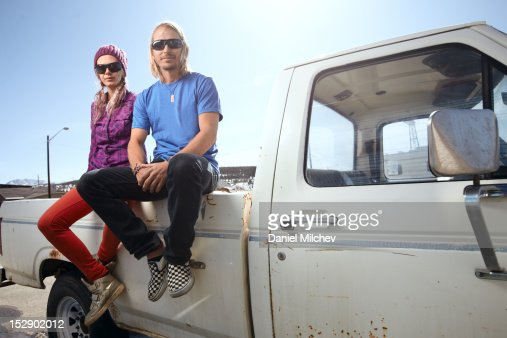 Couple sitting on the back of a truck. : Foto de stock