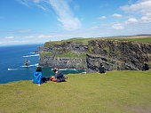 Couple sitting on the Cliffs of Moher, Ireland